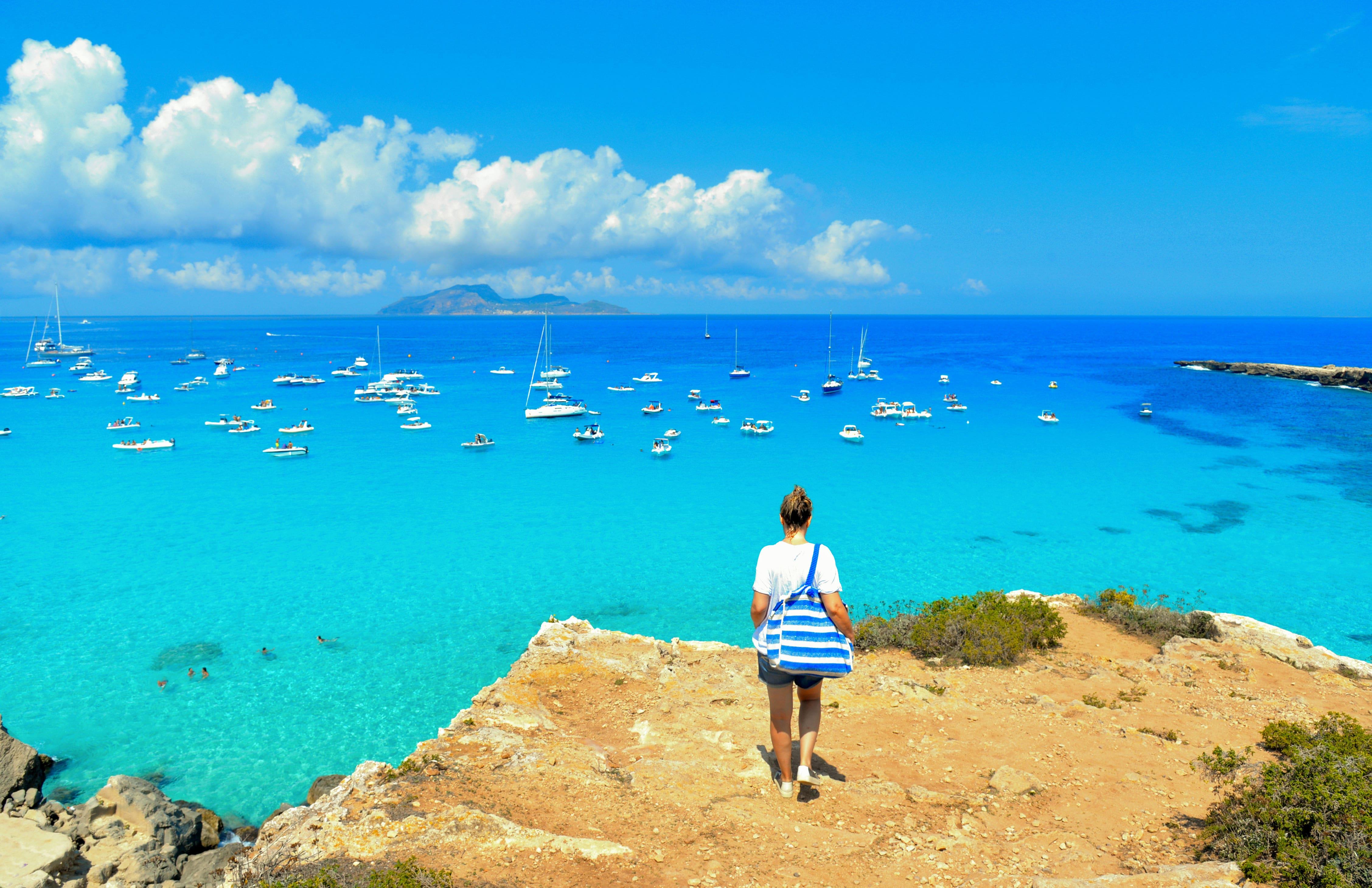 beach Cala Rossa on Favignana Island with small boats and Island Marettimo in background, Sicily Italy